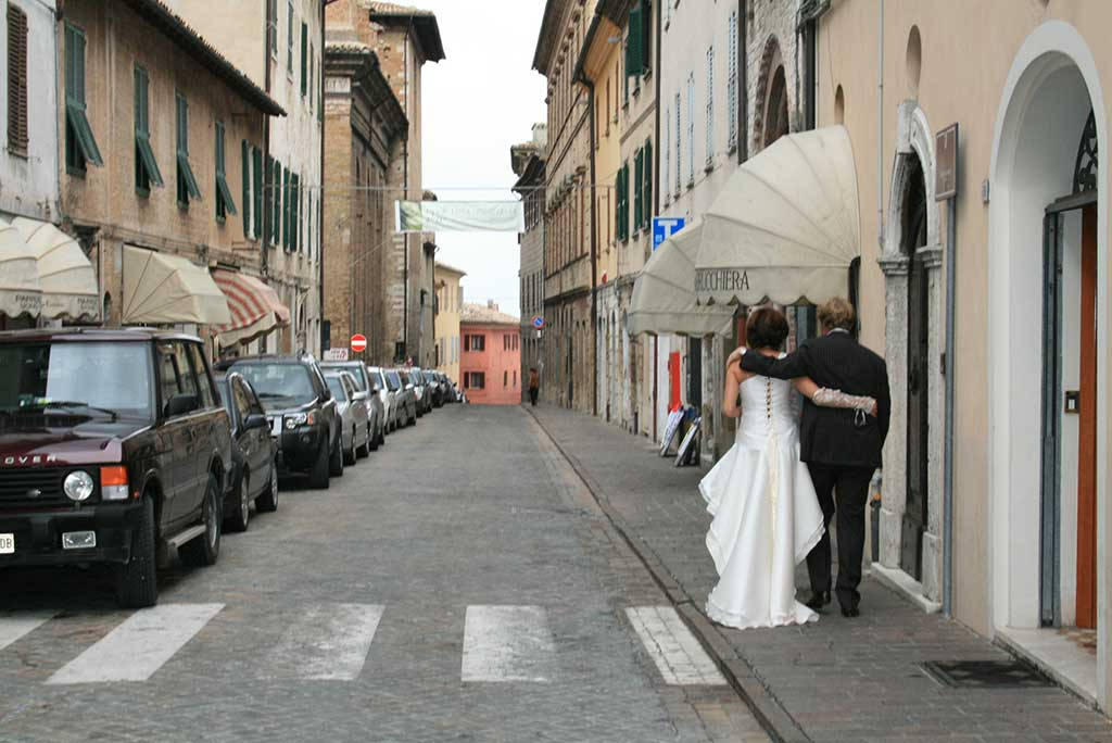 wedding coupple walking down the street in le marche